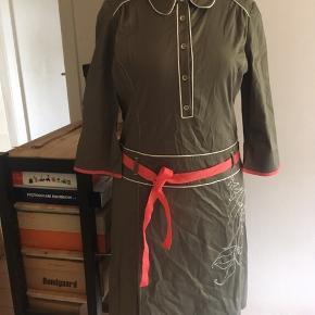 Smuk ny kjole fra By Groth.  Olivenfarvet flot stof med en anelse stretch, som sikrer en skøn pasform. Smukke råhvide satin pipingkanter og råhvide broderier og kontrastsyninger på front og ryg.  Skjult lynlås i siden, så den er nemmere at få over bryst og hofter. Rustikke metalknapper fortil og sødt koral-farvet aftageligt bindebånd, der matcher ærmekanterne.  Str. XL, men da den er lille i størrelsen, er figursyet og sidder meget til, vil den ca. passe en str. 40/42 med en medium barm eller en str. 44 med en mindre barm.  En utrolig smuk kjole med de fineste detaljer. Skriv pb for ekstra nærbilleder. Nypris kr. 1499,95.  Pris ved afhentning Nordsjælland eller + porto.