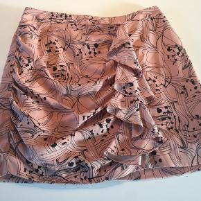 Lysrosa/pudderfarvet nederdel m/flot drapering og flæser fortil. Synlig lynlås bagpå.   En str. 40, jeg synes nærmere det er en str. 38.  100 % polyester.