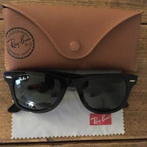 Ray Ban 'Original Wayfarer' - Polarized sælges. Solbrillerne er i tæt på ny stand, da de kun er brugt få gange. De er købt med polaroid glas, som fjerner genskær og reflektion i glassene. Der medfølger både kvittering og originalt etui (brunt læder). Brillerne er endvidere købt i størrelsen 50-22.  Brillerne er købt i 2016.