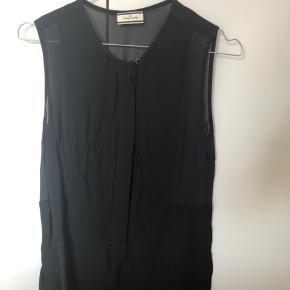 Fin bluse uden ærmer med sølvknapsdetalje øverst. Blusen har knapper fortil. Blusen kan passes af str. 34-38
