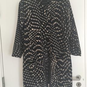 Lækker jakke/cardigan i sort/creme. Str er L, men den er snarere en XL. Krølfri kvalitet i viscose/elastan. Kan også bruges som kjole.  Prisen er fast 600 kr., og jeg bytter ikke.