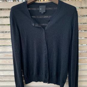 Klassisk sort cardigan (Ulla) i fin merinould fra Six Ames. Str. L. Fin kvalitet, kan bruges hele året. Lukkes med trykknapper, fastgjort på fint bomuldsbånd.