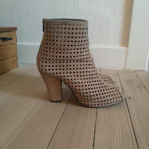 Fede sandaler med høje hæle og i perforeret ruskind. De almindelige i størrelsen og har en hælhøjde på ca. 9 cm og et indvendigt plateau under forfoden på ca. 1,5 cm. Sidder godt på foden. De lukkes med en lynlås bagpå.  De er brugt en del, men er velholdte og har stadig mange kilometer i sig. Sælges fordi, jeg bare må erkende, at jeg ikke længere gider at gå i høje hæle særligt tit, så der skal luges ud i samlingen.  Jeg handler gerne via Mobile Pay, men på købers eget ansvar!