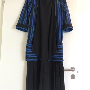 """Mega retro kjole med påsyet jakke i sort og blå. """"Sættet"""" er fra England og er sandsynligvis produceret i 80'erne. Kjolen er loosefit.  Længde: 113 cm Bryst: Ø 114 cm  Materiale: 100% polyester Købt i Vintage butik i København."""