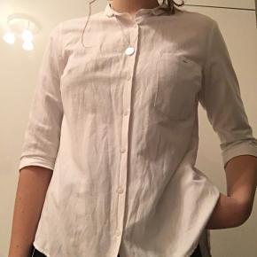 En flot hvid skjorte med trekvartærmer. Den har en flot ryg som går op i et V. Skjorten kan både bruges til hverdag, men også til formelle formål. Den er kun blevet brugt et par gange og er i fin stand. //Prisen er eksklusiv fragt//