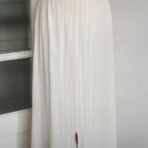 Superflot nederdel fra Masai. Farven er lys flødefarvet. Nederdelen har slidse både foran og bagpå + flotte bisse-læg midt foran. Materialet er 100 % viscose.  Livvidde: 35 cm x 2 + (elastik i livet) Længde foran: 70 cm Længde bag: 79 cm.  Ingen byt, og prisen er fast