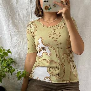 Grøn vintage bluse med blomster og andet mønster. Købt i en vintagebutik. Passes af en størrelse S/M, ses på en størrelse S på billederne.  Se også mine andre annoncer, jeg giver mængderabat🧚🏼♀️✨  Søgeord: vintage, retro, genbrug