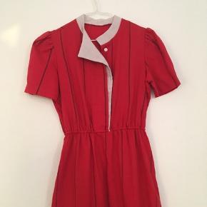 Smuk og helt unik vintage kjole købt i Amsterdam. Rød med diskrete lodrette striber. Den har meget fine detaljer ved kraven, ærmerne og knap-lukningen foroven. Der er elastik i indsnittet ved taljen og en lille slids i skørtets venstre side.