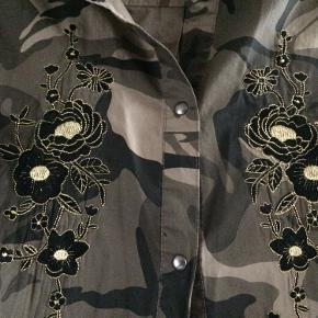 Camouflage skjorte med søde blomster applikationer.