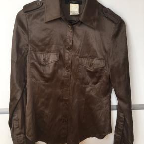 Fin silkeskjorte fra Weekend Max Mara sælges. Har et par år på bagen, men er kun brugt 2-3 gange.   Farven er en mellemting mellem brun og olivengrøn. Fine detaljer ved skuldrene + to brystlommer, lettere figursyet.   Superblød og lækker at have på, 96 % silke, 4 % elastan.  Bytter ikke, men sælges for 250 + porto med DAO.