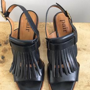 Flot sandal med 5,5 cm hæl.  Lidt stor i størrelsen. Der er lettere brugsspor under sålerne, men fremstår ellers som nye. Nyprisen var ca. 2000,-