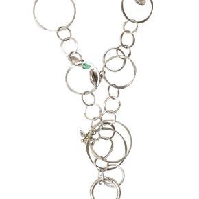 Varetype: -=NY=- GARDEN LANG HALSKÆDE Størrelse: 85cm Farve: Sølv Oprindelig købspris: 900 kr.  A&C JEWELLERY GARDEN LANG HALSKÆDE  2032-1406  Skøn halskæde sammensat af læderbånd og sølvfarvet ringe med mange flotte vedhæng i grøn og lilla. Halskæden er fra Garden kollektionen, hvilket tydeligt kan ses på de søde vedhæng. Der er bl.a. et pindsvin, en snegl, en bi og et blad.   Længde: ca. 85cm Model: Garden Style: 2032-1406   Varens stand: aldrig brugt