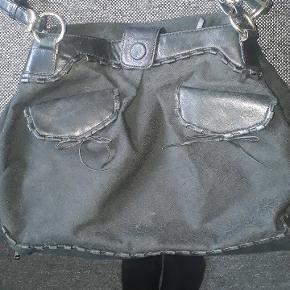Flot taske med to store lommer delt af en lomme med lynlås. Tasken kan enten bæres i de to hanke som kan spændes ind og ud men man kan også få den op til skulderen.