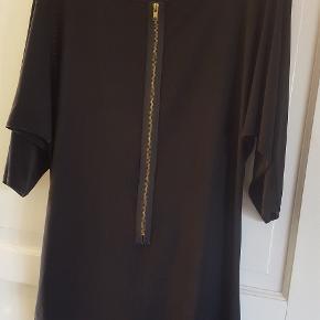 Sort bluse fra Freequent i str. 42,   Lang sort T-shirt/bluse med pynte lynlås foran. Den er lidt gennemsigtig.  Str. L