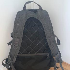 """Mørkegrå Evanz Eastpak taske med lyse læder detaljer. Der er plads til en drikkedunk i siden på tasken. Et dejligt stort rum bagerst med plads til pc og lidt bøger. Det midterste rum er der plads til fx. madpakke. Foran er der to rum med plads til penalhus og mobil. På ryggen af tasken er der et lille rum til nøgler og div. ting.  Mål: 52 cm høj, 29 cm i længden og dybden er 19 cm. Der er plads til en 15,6"""" pc. Tasken blev købt d. 10 september 2019, men har kun været i brug i 1/2 år - og er ikke beskadiget. Unisex taske. Skriv for flere billeder."""