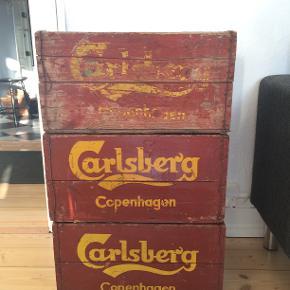 3 stk. antikke Carlsberg-ølkasser. De er alle helt den samme model, to der er komplet ens, og en sidste der har lidt mere patina. De har nøjagtig samme mørkerøde farve, og gule logo. De er alle i virkelig fin stand ift. hvad man ellers kan finde på loppemarkeder. Originalpris var 350,- stk. Jeg bruger dem som bord i stuen, da de stablet på hinanden har en perfekt højde til en stuelampe og til opladerstation af mobil. Jeg sælger dem, da jeg skal flytte, og desværre ikke får plads til dem. Mål: brede 48 cm, højde 25 cm, dybde 30 cm