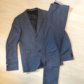 Flot jakkesæt fra Tommy Hilfiger. Brugt 2-3 gange. Både habitjakke og bukser er str. 48. Taske medfølger. Kommer fra ikkeryger hjem. BEMÆRK hul på bagdel. Det er repareret og ses ikke når bukserne er på. Derfor er de sat billigt.