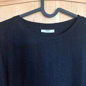 Sort bluse med stribet stof som giver den lidt mere liv.  100% polyester