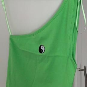 Grøn (lime/neon) asymmetrisk One shoulder top fra UO med lille ying-yang logo i str S. Har den også i M & XS - se andre annoncer. Materiale er 100% blød bomuld. Længde i den lange side ca 44 cm og den korte uden skulderstrop ca 24 cm Bredde ca 30 cm og kan streches til mere end 42,5 cm i bredden. Porto r 20,- såfremt brevpost via Postnord