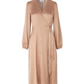 - Lange ærmer - Wrap kjole - Blankt materiale - Midi længde - Sart brun med gule prikker - Materiale: 100% Viskose