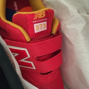 New Balance 373. Sprit nye, aldrig brugte røde sko med gule detaljer. Velcrolukning.   Fejlkøb.   Er absolut ikke kun til drenge, men Trendsales kan ikke skrive begge køn.   Kan afhentes i Kbh nv
