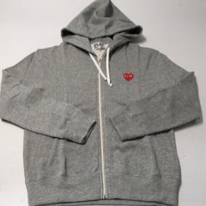 Hej. Jeg har denne CDG PLAY zip up hoodie, som jeg har fået i en mystery box. Det er en størrelse M, men som i nok ved er CDG et nummer mindre, end, hvad der står. Det ville sige den praktisk set er en small😊  Den koster 1935 kr. for ny, og er som sagt ALDRIG brugt.