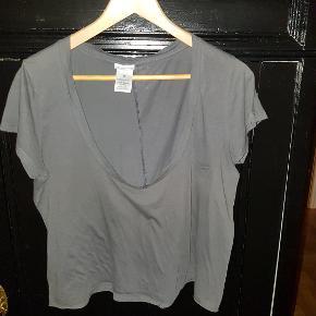 """Blød mavebluse med korte ærmer og dyb halsudskæring - kan med fordel bæres skråt for et """"off-shoulder"""" look."""