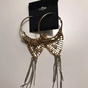 Flot smykkesæt bestående af store øreringe med guldudsmykning og sølv kvaste, og en halsnær halskæde.   Sælges samlet eller hver for sig.  Ikke ægte guld.   Kan afhentes i Vejle eller Århus C, eller sendes på købers regning.