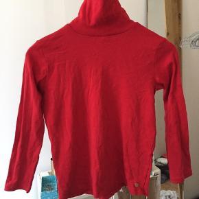Rød højhalset bluse.