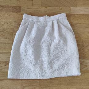 Skøn nederdel i perfekt stand i jacquard lignende stof. 2 lommer foran. Farven er meget svagt rosa