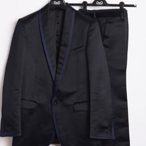 Mørkeblå tuxedo fra Dolce & Gabbana, str 48. Kun brugt 3 gange, er derfor så god som ny. Ydersiden består af 36% silke og 64% polyester, indvendigt er det 100% viskose. Nypris 16.500 DKK. Sælges for 4500 DKK. Skriv for flere billeder.