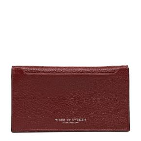 Wallet in grainy leather Contrast lining in smooth leather Open pocket at back Inside features three open pockets, one zipped pocket and seven credit card slots Embossed Tiger of Sweden logo Size: 9 x 15.5 cm