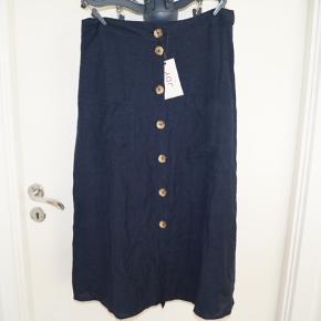 Fin nederdel, går til lidt på skinnebenet på mig (168cm). Der er to lommer og knapper hele vejen ned.  Det er en str. 36, men passer en 38