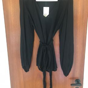 Bluse med ballonærmer, v-udskæringen og bindebånd i taljen. Blusen er i et luftigt materiale med tynde sorte striber på langs. Blusen er aldrig brugt og har stadig prismærke i. Den fremstår derfor fuldstændig som ny.
