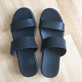 Kan desværre ikke se mærket på sandalen. Sort med let glimmereffekt  i - god stand!  Desværre lidt for store til mig.
