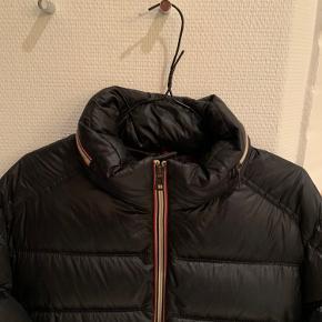 """Kom endelig med BUD!! Str. 4! Moncler jakke, som er perfekt til vinteren  Har ingen tags eller lign. men kan vise jer dokumentation af, at jakken er ægte.  De eneste """"fejl"""" ved jakken er den ødelagte tegneserie inden i jakken, samt lidt tegn på slid inde i jakken, som også ses på billedet. Derudover er der lavet en lille sygning, hvor der er kommet et """"plaster"""", som nærmest ikke kan ses, da det matcher farven.  Skriv endelig pm, hvis I skal have flere billeder"""
