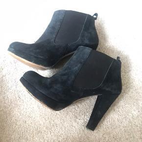 Sælger disse populære og enormt fine heels fra Ganni, da de desværre er for store.  De er af ægte ruskind, der er farvet mørkeblå, og med elastik i siderne der gør det lettere at få poterne i dem.  De har en lille fejl i hælen, der kan fixes ved en skomager. Men derfor sælges de billigt (se billede)  De passes af en 39 💃🏼