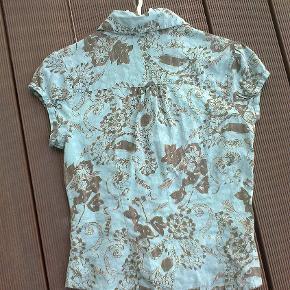 Varetype: kortærmet skjorte sommer bluse blomstret blomster mønstret Farve: grøn  100 % bomuld.  Brugt 1 gang.  Porto er sendt som forsikret pakke med Dao, med mindre andet aftales.