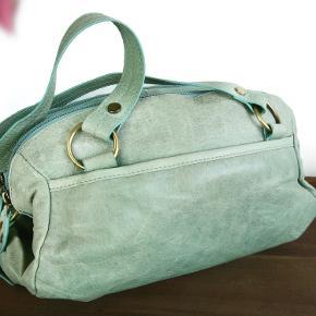 Lækker kvalitets taske i blødt skind fra Oxford Bags. Indeni har tasken stort rum, flere mindre rum, hvoraf 1 med lynlås. Mål 32x16x13cm.