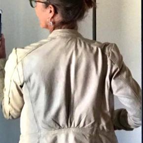 """Handskeblød skindjakke med fede detaljer både foran og på ryggen. I jakken står der str 38, men den er lille i størrelsen. Har to lommer med trykknap og en inderlomme.  Se også alle mine andre ting til salg ved at søge på """"lykkevi""""🙏😊   Kun brugt 5-6 gange, har ingen slid eller pletter.  Se også mine andre fine ting under lykkevi🌞 De flotte denimbukser med simili og de sorte sandaler vil passe perfekt til foråret og til jakken👍"""