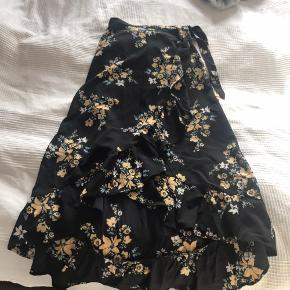 Lang nederdel der går på op foran. Aldrig brugt, mærket er dog taget af. Lukkes med en knap og et bånd i siden