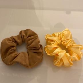 2 styks fine scrunchies sælges samlet. Ene i beige stof, andet i gult satin-lignende materiale. Købt i London.  Kan også sendes med PostNord for 10 kr.