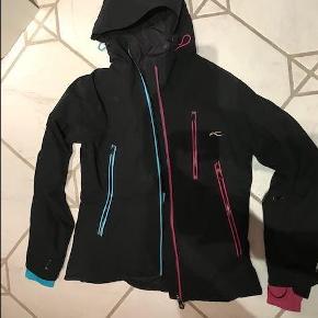 """Dame skisæt fra Kjus. Jakke str. 38 / buks str. 36. Ubrugt / som nyt. Sættet er sort, men jakken har en flot turkis og rosa """"indmad"""" ved ærmer samt lynlåse. Skitøj Farve: Sort Oprindelig købspris: 8000 kr."""