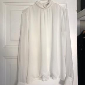 Hvid bluse med høj hals. Knapper hele vejen ned af ryggen. Gennemsigtig bagpå, dobbeltstof foran.