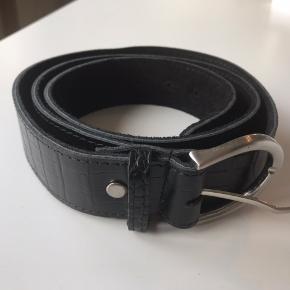 Tim & Simonsen læderbælte med krokodille print.  Sort ægte læder Måler 120 cm 4 cm bredt Aldrig brugt   UNISEX