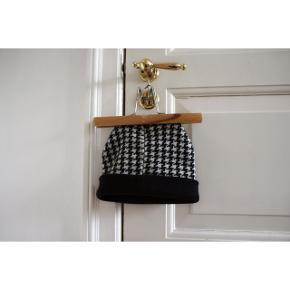 Mønstret hue  - Houndstooth mønster  - 50% uld - Farve: sort og hvid  Pasform: - Huen kan foldes i kanten, og derfor kan den passe de fleste  Styling: - Passer godt til klassisk tøj(langer frakker, læder støvler, blazers mm.) da huen selv er i et klassisk mønster. Den kan også styles street sammen med en ruskindsjakke fx. (Se billede 2)