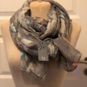Super sødt tørklæde i lysegrå med sommerfugle i div. farver. Tørklædet måler ca. 90 x 200 cm. Nyt og ubrugt og stadig med prismærke på.  Byd :-)