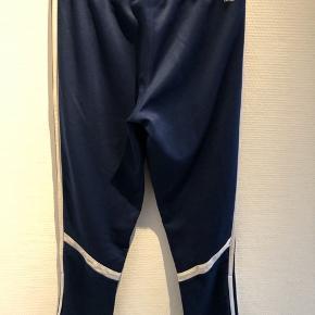 Adidas træningsbukser i blå med hvide striber. Der er et par små pletter på en hvid stribe. Størrelsen er klippen af men bukserne måler 63 cm i indvendig benlængde  og 81 cm i udvendig benlængde.
