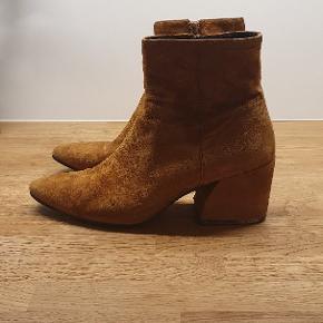 Vagabond støvler i modellen Olivia i farven Lion. Fås stadig i butikkerne. På hælen (under sålen) er skindet gået lidt op i kanten på begge hæle, som det ses på billedet 3. Derudover ganske lille ridse på snuden, som også anes på billede 2. Ellers fin stand udenpå.