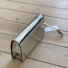 Metallic sølv clutch. Lomme bag på samt to rum inden i. Aftagelig håndledsstrop.  Mål 25 x 15 cm.